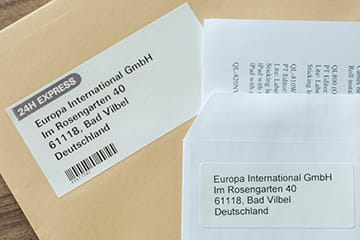 Brother DK die-cut label next to a Brother DK continuous length label stuck to envelopes