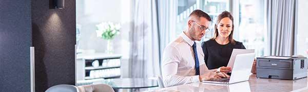 homme et femme assis au bureau sur un ordinateur portable