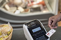 Brother QL-82NWB on deli counter with label printed